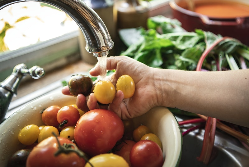 A person's hand washing vegetables in the kitchen's sink