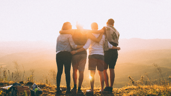 Four people looking at the sunset with their backs looking at the camera