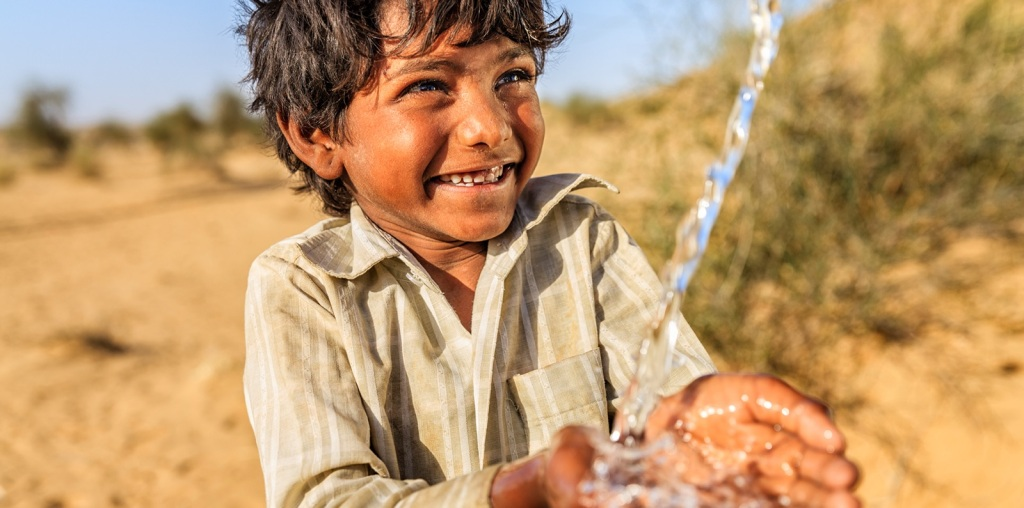 A young child smiling while drinking water from his hands
