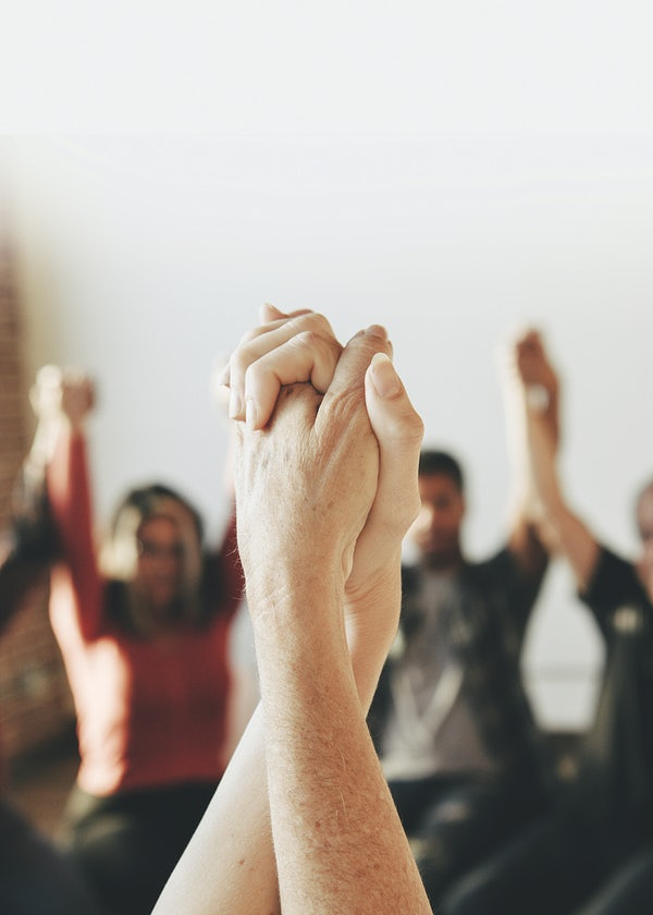 Two hands raised in the air grabbing each other with other people also raising their holding hands in the air together in a circle in a background