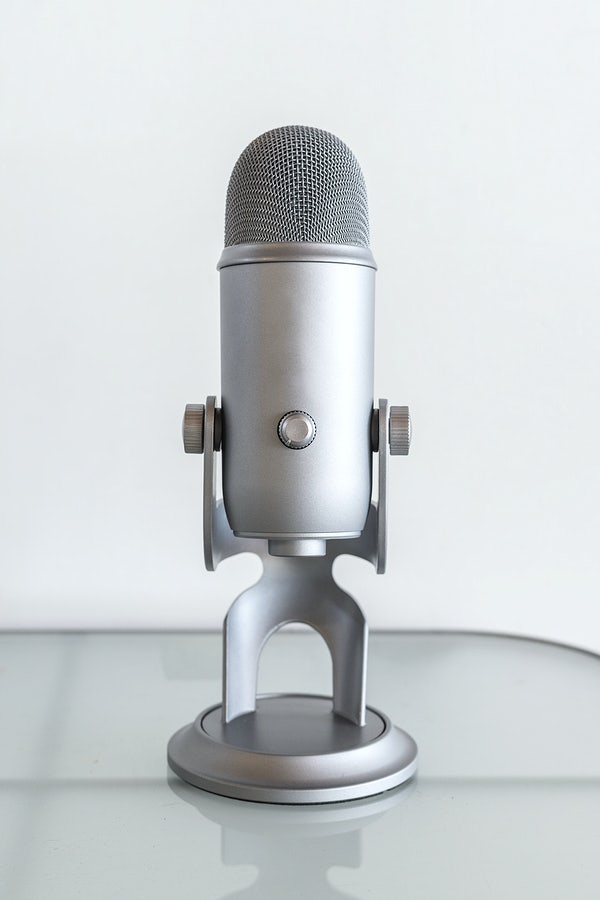 A microphone standing in a table with a white background to represent sharing one's voice