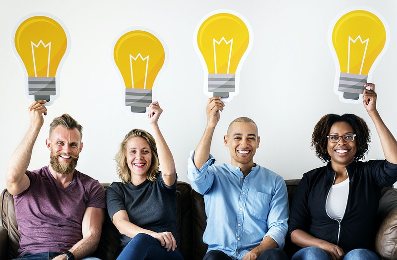 Two women and two men each holding a big image of a lightbulb while smiling to demonstrate how diversity leads to greater creativity
