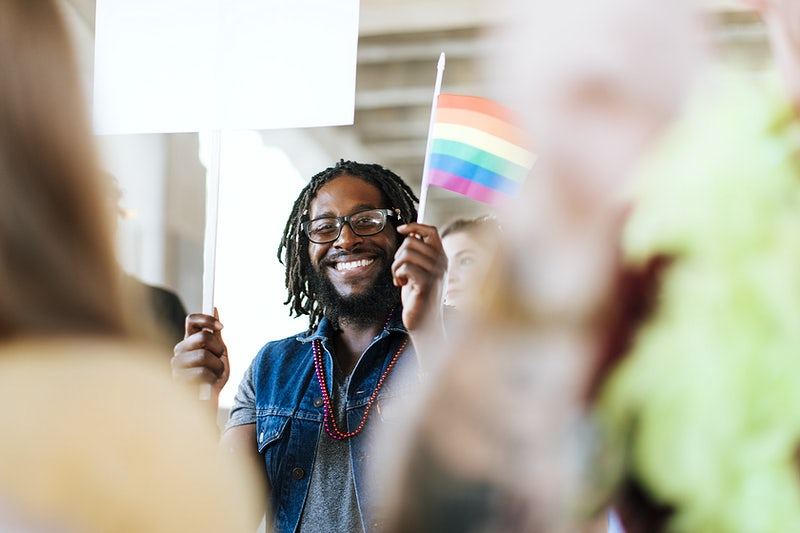 An African American smiling and holding a flag of different colors to represent diversity and inclusion