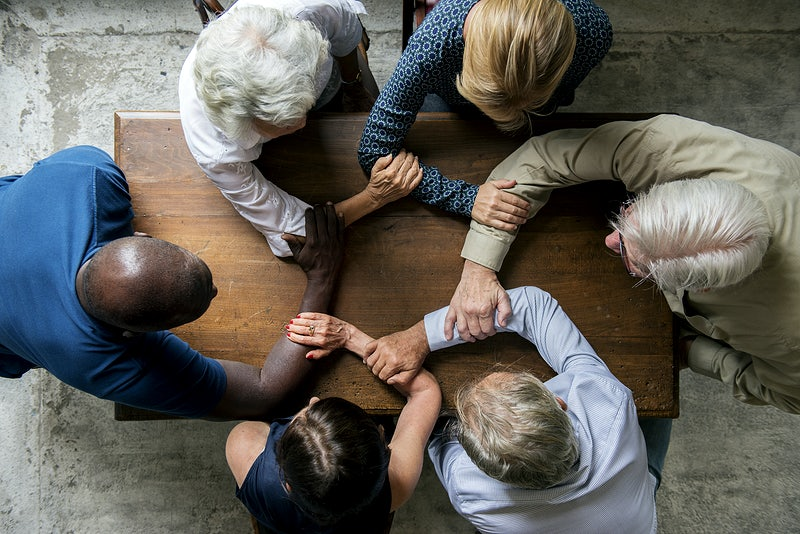 A group of people from all background and ages sitting in a table grabbing each other's hands to symbolize diversity and inclusion