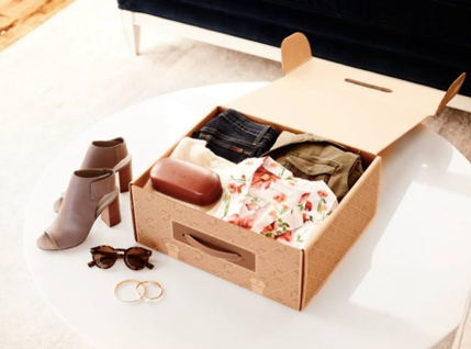 A shoe and clothing subscription box opened with the products being showned