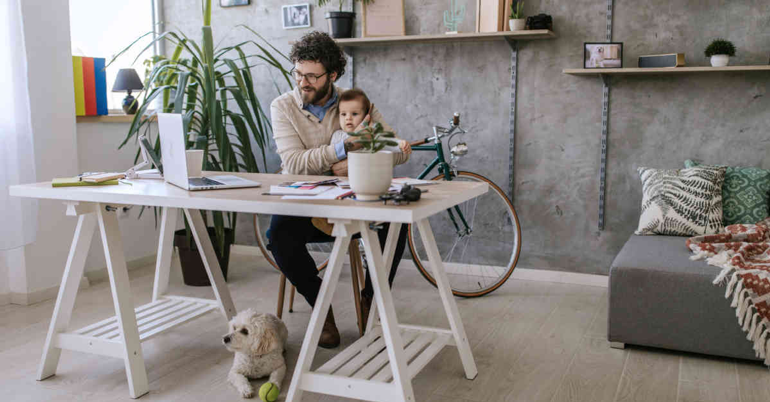 A father working from home with his dog and his baby son to represent the importance of a healthy work-life balance